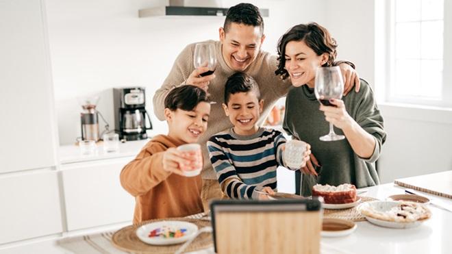 Família com copo na mão reunida em videochamada durante a Páscoa