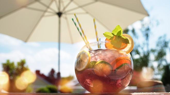 Copo de cocktail com lima e palhinhas numa esplanada ao sol