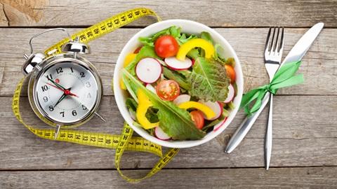 taça com salada, fita métrica e talheres usados no controlo de peso