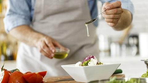 homem a temperar salada com uma colher de azeite