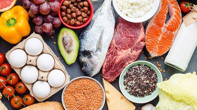 mesa com tomates cherry, pimentos, ovos, uvas, abacate, peixe, carne, salmão, frutos secos