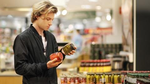 Homem num supermercado analisa a rótulos de frascos para procurar produtos sem glúten