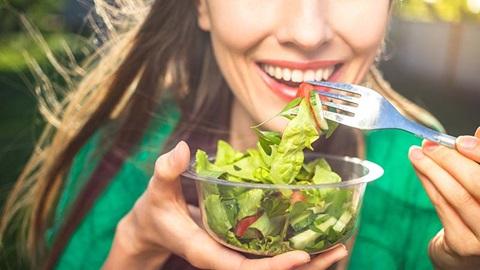 mulher a comer salada de uma taça