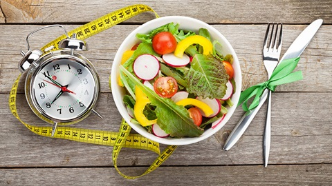 prato com salada de vegetais, relógio analógico, fita métrica, garfo e faca