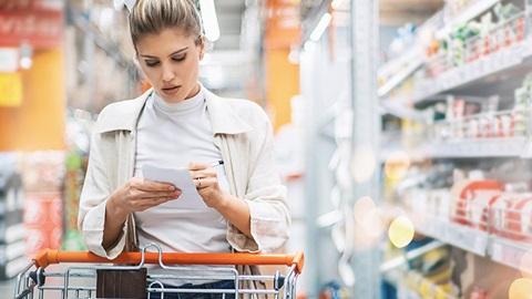Mulher no supermercado a ler o rótulo de um produto alimentar