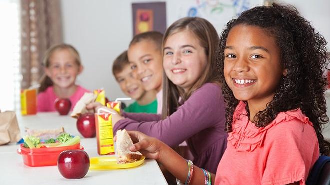 Cinco crianças sentadas à mesa a lanchar sandes, maçãs, sumos