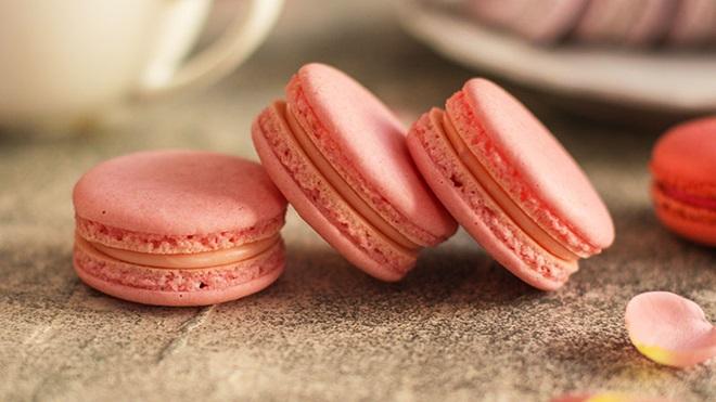 3 macarons cor de rosa em cima de uma mesa