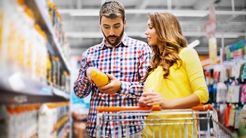 Casal num supermercado a ler o rótulo de uma garrafa