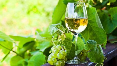 Copo de vinho branco e uvas brancas
