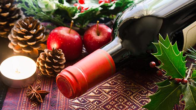 garrafa de vinho deitada ao pé de vela com decoração de Natal