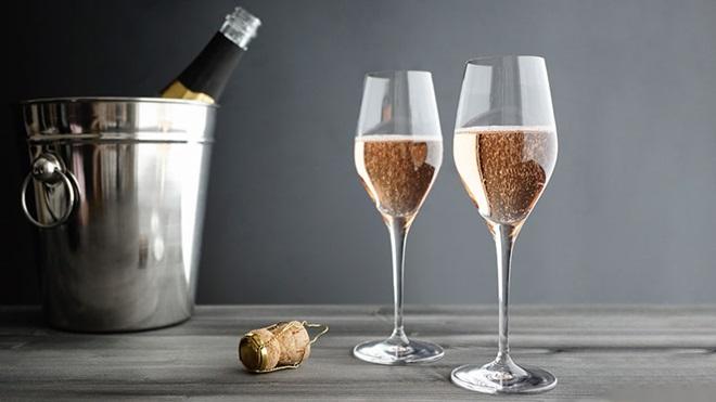 copos com espumante rosé, rolha e garrafa na mesa