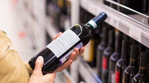 pessoa com garrafa na mão a ver o rótulo para comprar vinho
