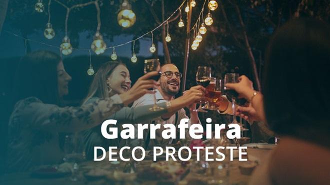 Várias pessoas a rirem e brindarem com copos de vinho e cerveja, sentadas a uma mesa de refeições, num ambiente noturno no exterior, com grinaldas de lâmpadas penduradas acima das suas cabeças