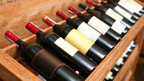 Uma estante de madeira própria para garrafas de vinho, com várias garrafas de vinho tinto deitadas.