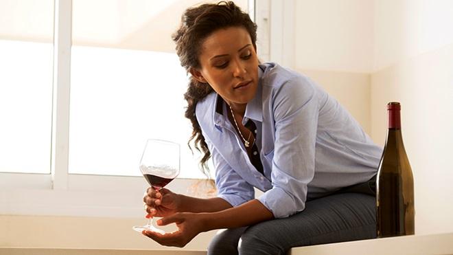 Mulher sentada com copo de vinho na mão e garrafa ao lado