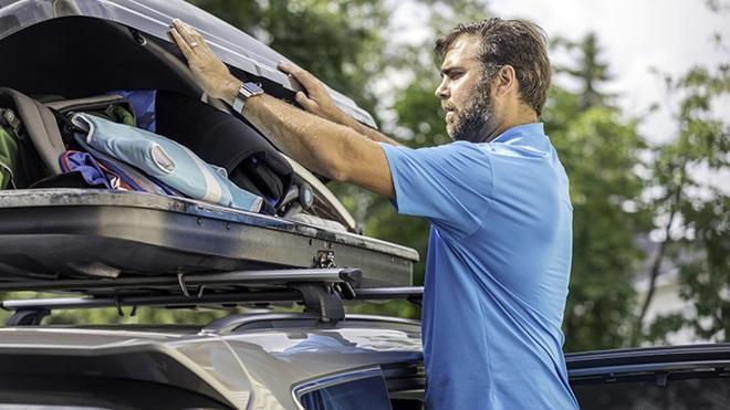 homem a carregar bagagem em caixa no tejadilho do carro
