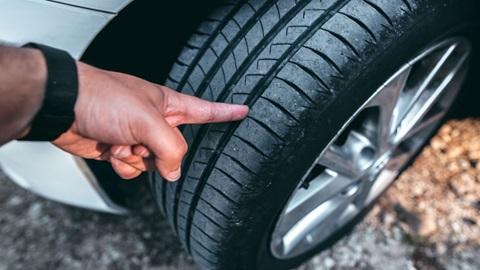 mão a apontar para desgaste na borracha do pneu