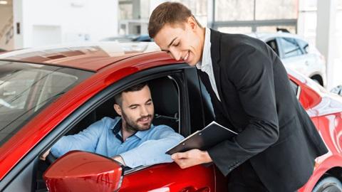 Homem ao volante de carro usado e vendedor apresenta-lhe valor da compra