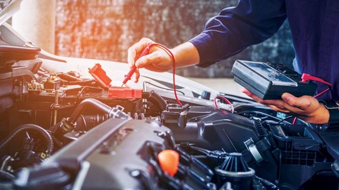 mecânico a verificar motor de carro na oficina