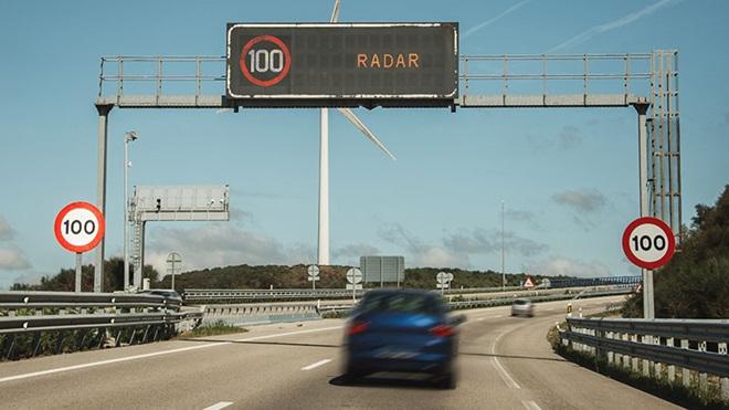 carro a passar por pórtico de autoestrada que mostra informação de radar e limite 100 de velocidade