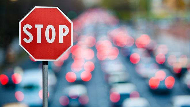 Sinal de STOP com estrada com carros em engarrafamento ao fundo
