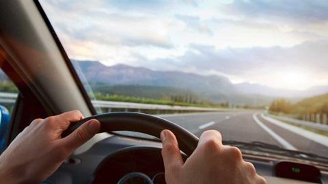 Vista do interior de um carro, com o volante e as mãos do condutor em primeiro plano, e uma paisagem com estrada, campo e montanhas em segundo plano.