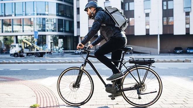 Homem a pedalar uma bicicleta elétrica numa rua junto a prédios