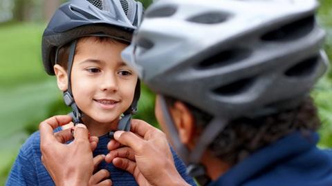 Adulto coloca um capacete de bicicleta a uma criança