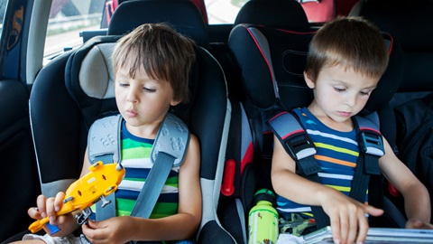 Dois meninos sentados em cadeiras auto instaladas no carro