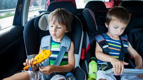 Dois meninos sentados em cadeirinhas auto para criança
