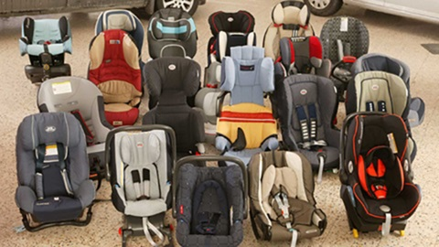 várias cadeiras de crianças para carro dispostas no chão