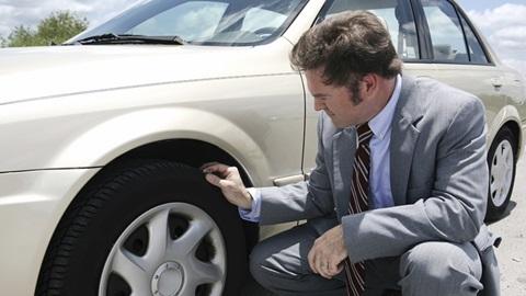 Homem a observar o estado do pneu do carro