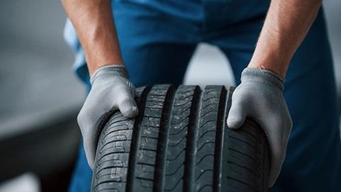 mãos de mecânico com luvas a agarrar um pneu