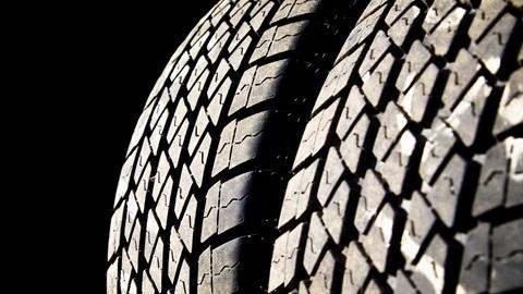 Plano de pormenor do relevo de um pneu sobre um fundo escuro.