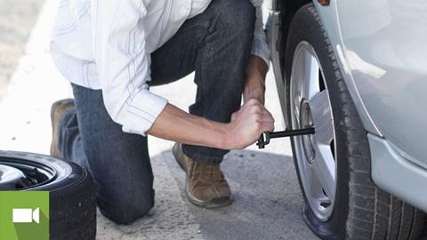 Homem a trocar um pneu furado