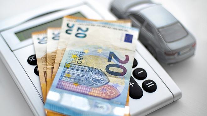 calculadora, notas de euro e carro numa mesa