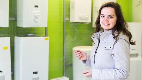 Rapariga de casaco claro a escolher o melhor esquentador numa loja com esquentadores brancos expostos numa parede verde.