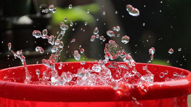Balde cheio de água, com gotícolas no ar.