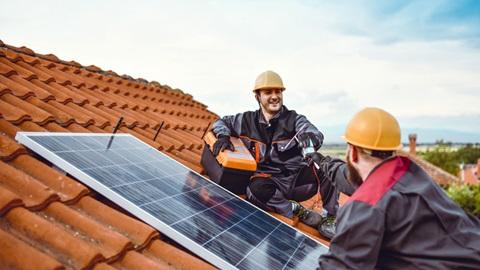 Dois trabalhadores no telhado a reparar um sistema solar térmico.