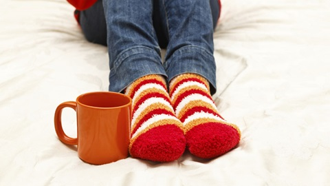 Pés com meias quentes às riscas ao lado de uma chávena cor de laranja com uma bebida quente