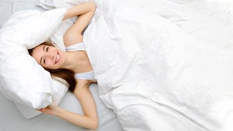 Uma rapariga deitada numa cama e tapada por um edredão. Está vestida de branco e sorridente, e ajeita a almofada com as mãos.