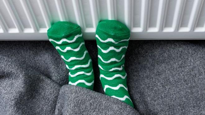 Pés com meias verdes e brancas encostados a um aquecedor