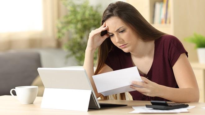 Mulher preocupada a olhar para papel e portátil