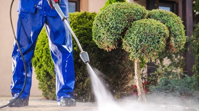 Homem a limpar o jardim com máquina de pressão