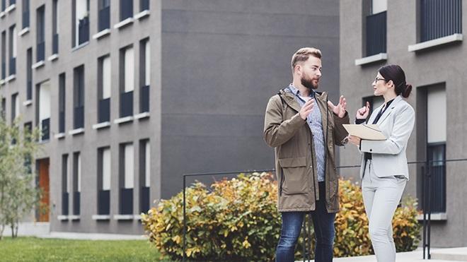 Homem e mulher conversam em frente a prédios de um condomínio