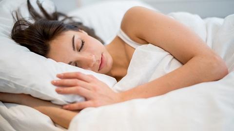 mulher a dormir de lado numa almofada