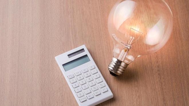 Lâmpada e máquina de calcular em cima de uma mesa