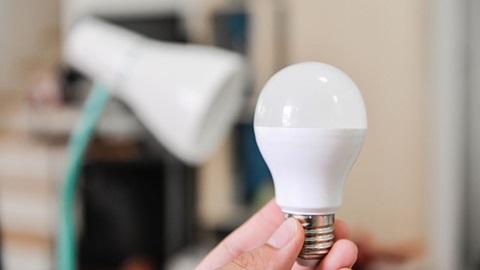 mão agarra lâmpada em frente a um candeeiro de mesa