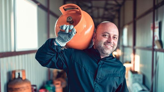 Homem a transportar botija de gás