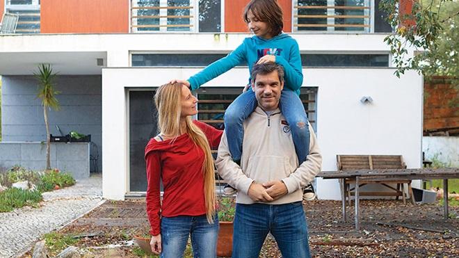 família de 3 pessoas à frente de casa com energias renováveis